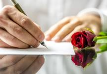Man writing love letter with rose sitting next to him